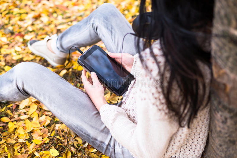 Jeune adolescente heureuse à l'aide de son comprimé et écoutant la musique dans le parc de ville d'automne Photo de mode de vie d images stock