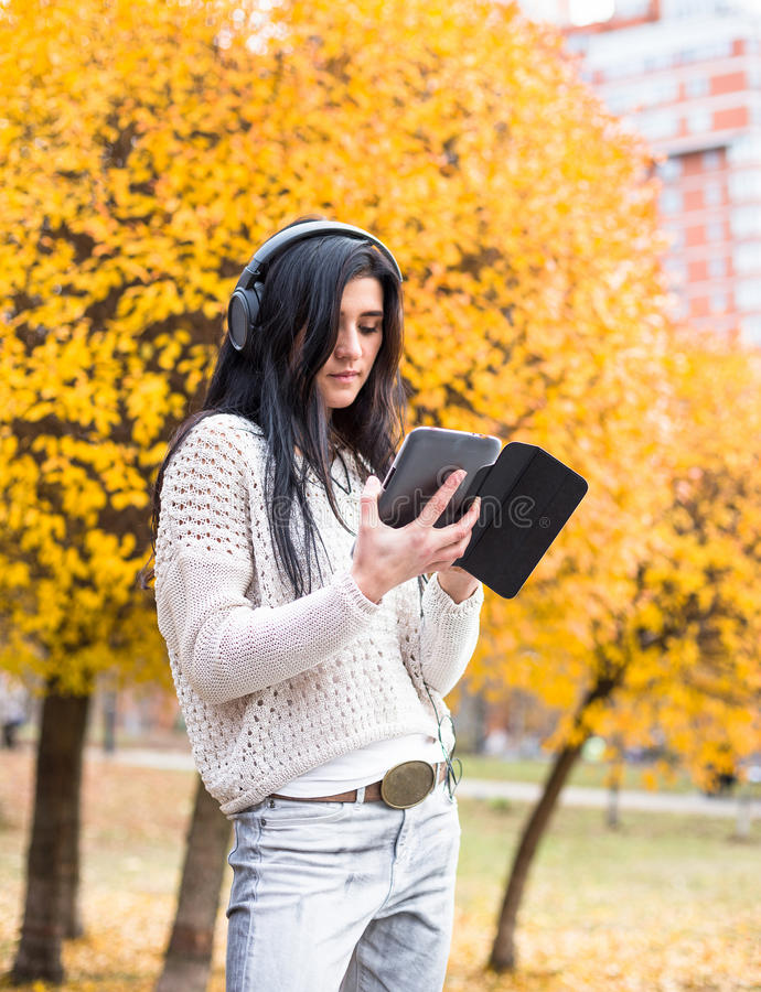 Jeune adolescente heureuse à l'aide de son comprimé et écoutant la musique dans le parc de ville d'automne Photo de mode de vie d photos stock