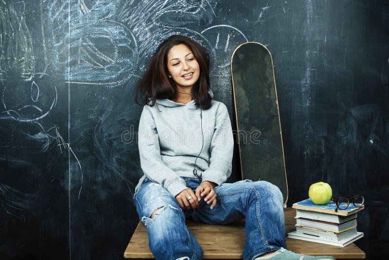 Jeune adolescente mignonne dans la salle de classe ? l'allocation des places de tableau noir sur la table souriant, concept moder images libres de droits