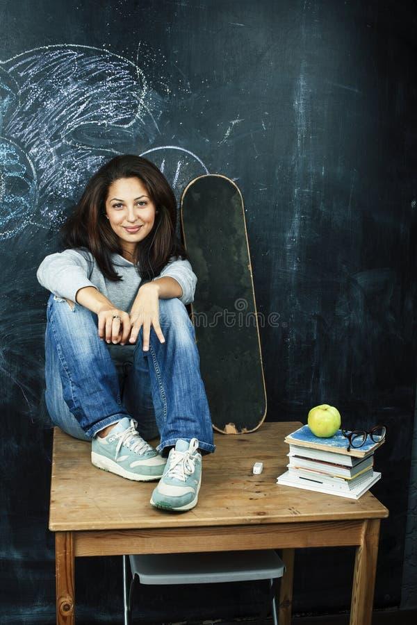 Jeune adolescente mignonne dans la salle de classe ? l'allocation des places de tableau noir sur la table souriant, concept moder image stock