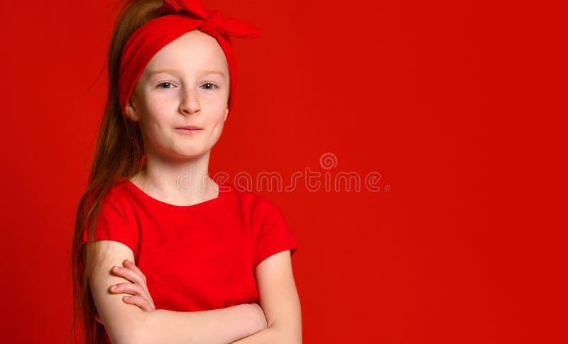 Jeune adolescente rousse douce avec la peau couverte de taches de rousseur saine, portant un dessus de r?servoir rouge, regardant photo stock