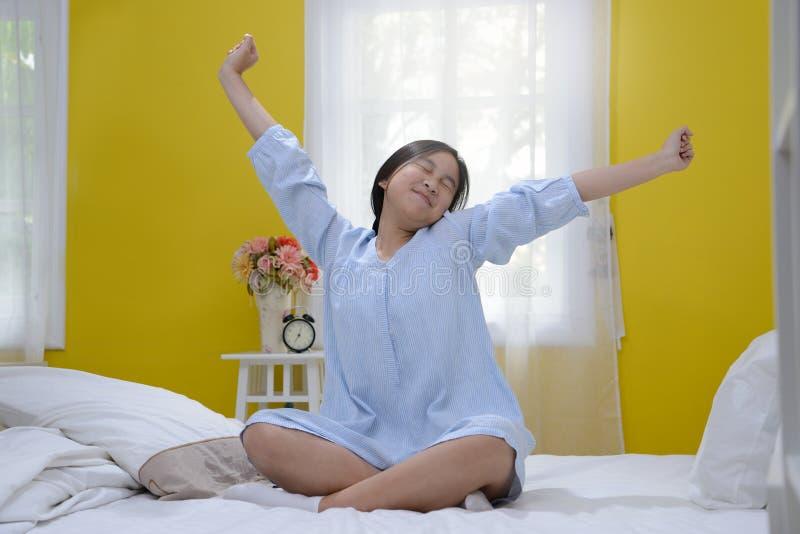 Jeune adolescente s'étirant dans le lit images libres de droits