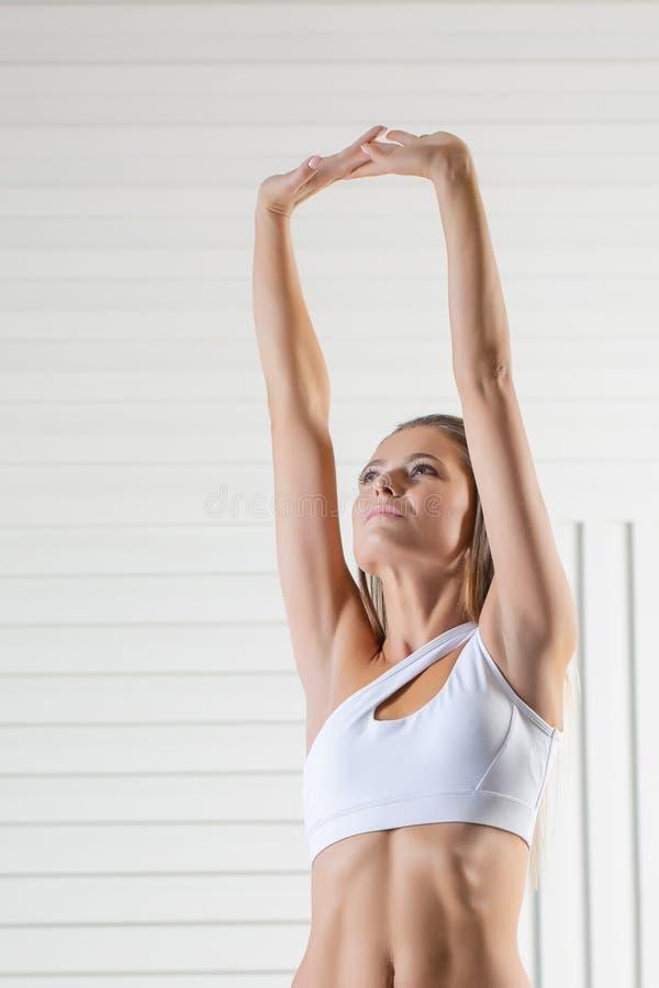 Jeune adulte attirant dans les vêtements de sport posant sur le fond blanc Femme sexy et sensuelle de brune avec le corps parfait image libre de droits
