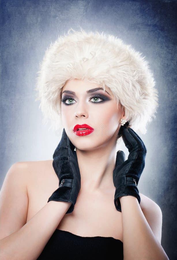 Jeune adulte caucasien attirant avec les gants noirs d'isolement sur le fond gris. Belle fille avec les lèvres rouges dans le chap photo libre de droits