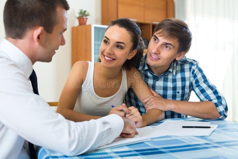 Jeune agent de couples et d'opérations bancaires à l'intérieur photographie stock libre de droits