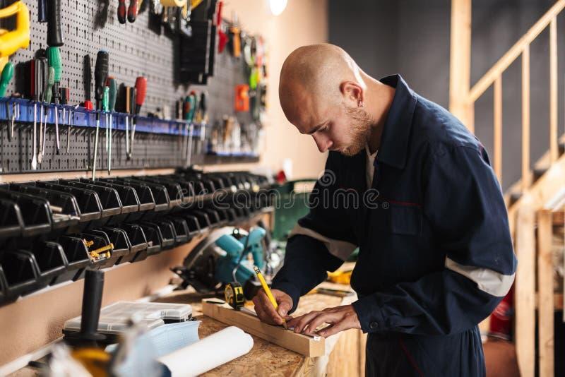 Jeune agent de maîtrise dans des vêtements de travail pensivement utilisant la bande de mesure image libre de droits