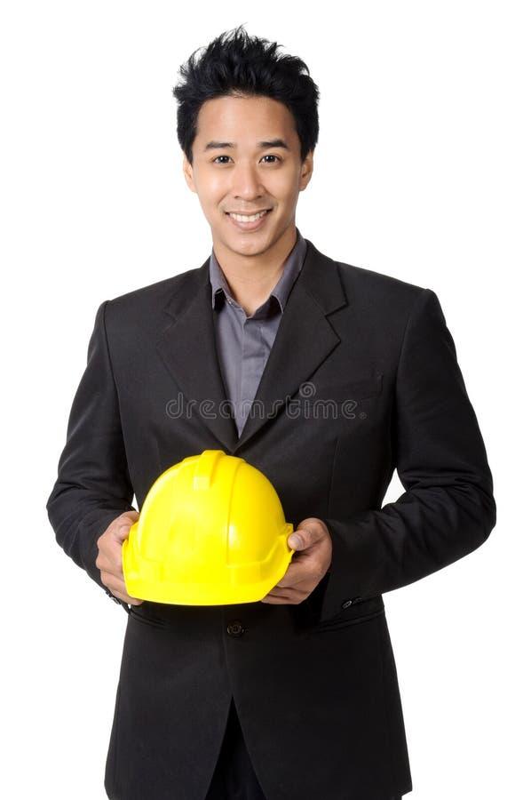 Jeune agent de maîtrise ou ingénieur avec le casque antichoc jaune dans le costume d'isolement photo stock