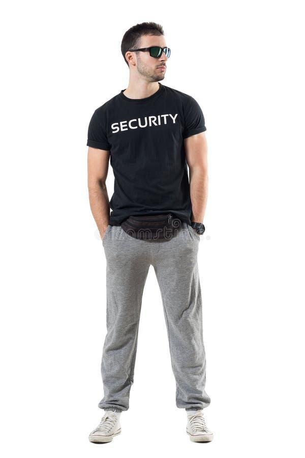 Jeune agent de police secret dur avec le sac de taille et lunettes de soleil regardant loin photographie stock
