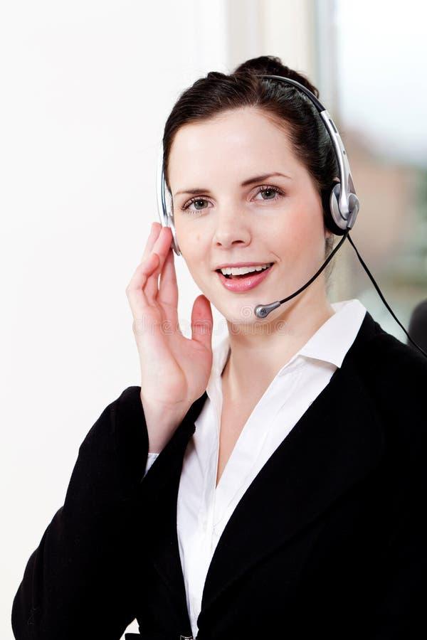 Jeune agent féminin de sourire de callcenter avec le casque photo libre de droits