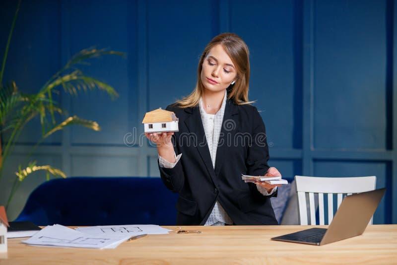 Jeune agent immobilier caucasien tenant l'argent et le modèle 3d de la maison dans des mains sur le fond bleu de mur photo libre de droits