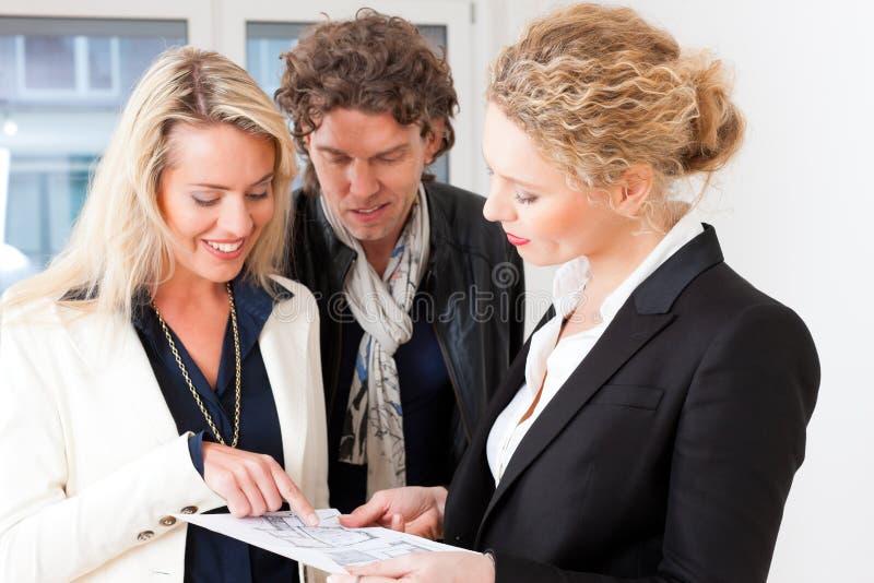Jeune agent immobilier expliquant le plan au sol aux couples photo libre de droits