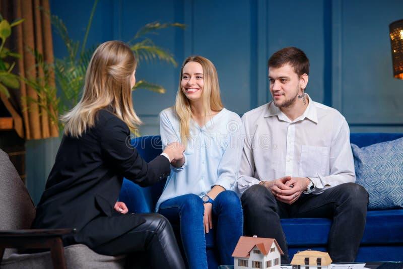 Jeune agent immobilier femelle ?l?gant donnant la cl? du nouvel appartement, maison aux couples caucasiens heureux photo stock