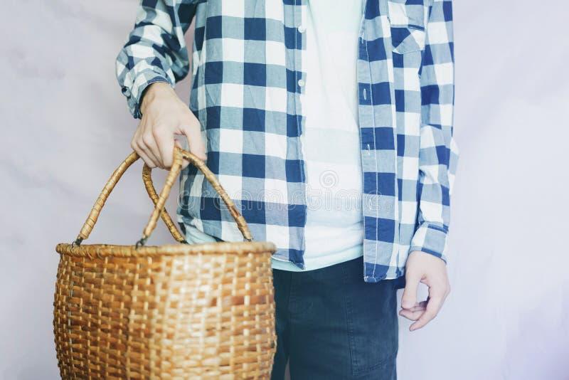 Jeune agriculteur masculin tenant un panier de récolte dans des mains, images libres de droits
