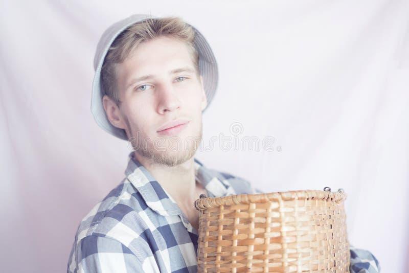 Jeune agriculteur masculin tenant un panier de récolte dans des mains, d'isolement photo libre de droits