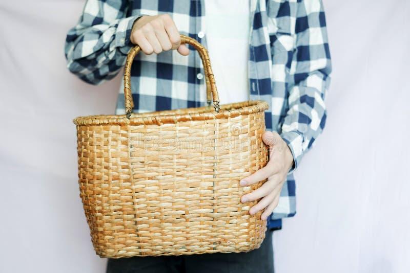 Jeune agriculteur masculin tenant un panier de récolte dans des mains, d'isolement image libre de droits