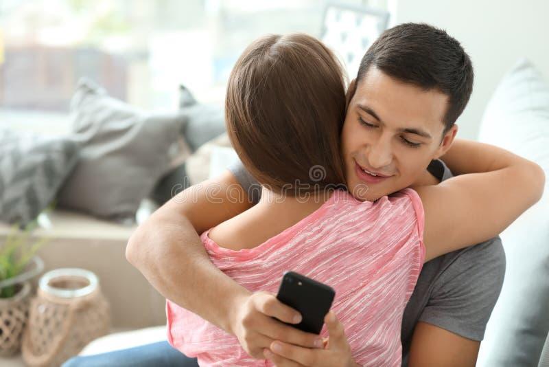 Jeune amant des textes de tricheur tout en étreignant son amie à la maison photos stock