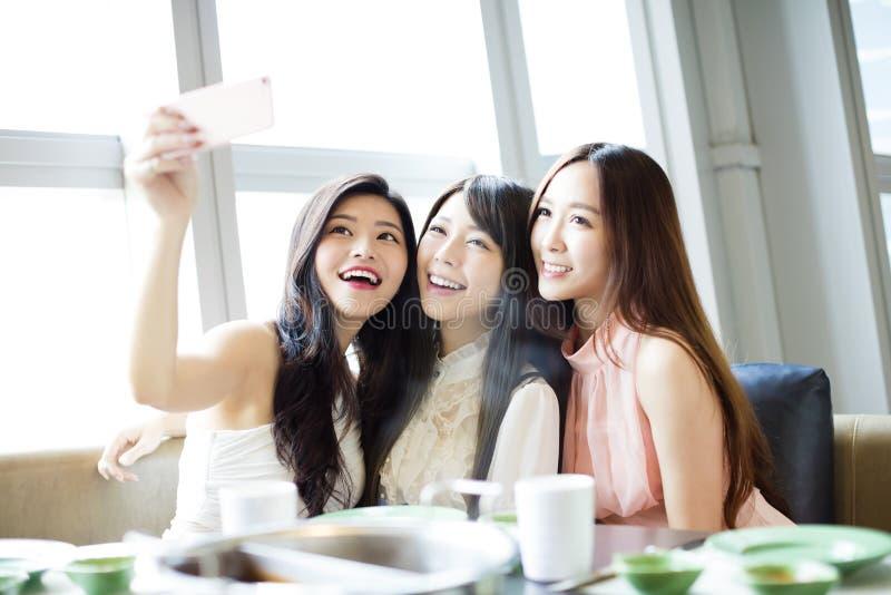 Jeune amie prenant le selfie ensemble dans le restaurant photographie stock