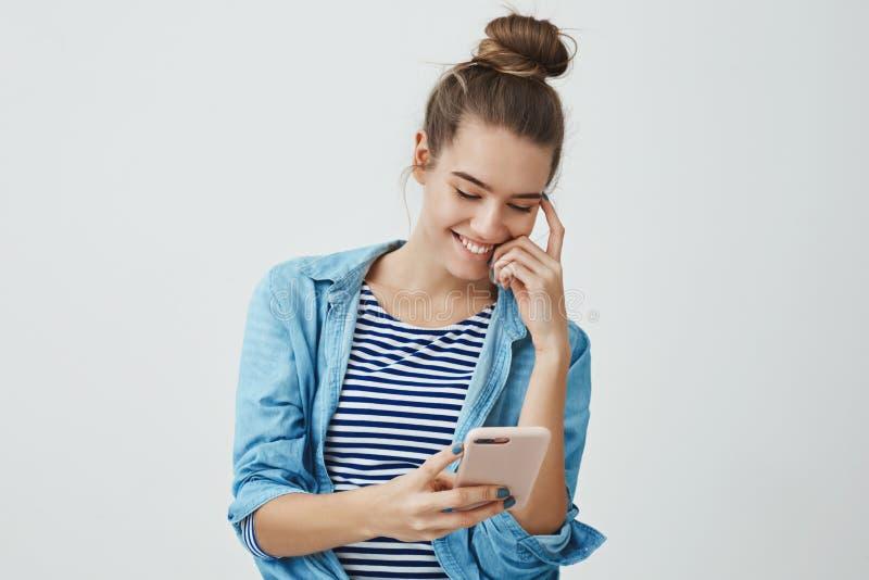 Jeune amie romantique européenne attirante insouciante 25s, hairbun confortable debout de vêtements lisant touchant le message  photo stock