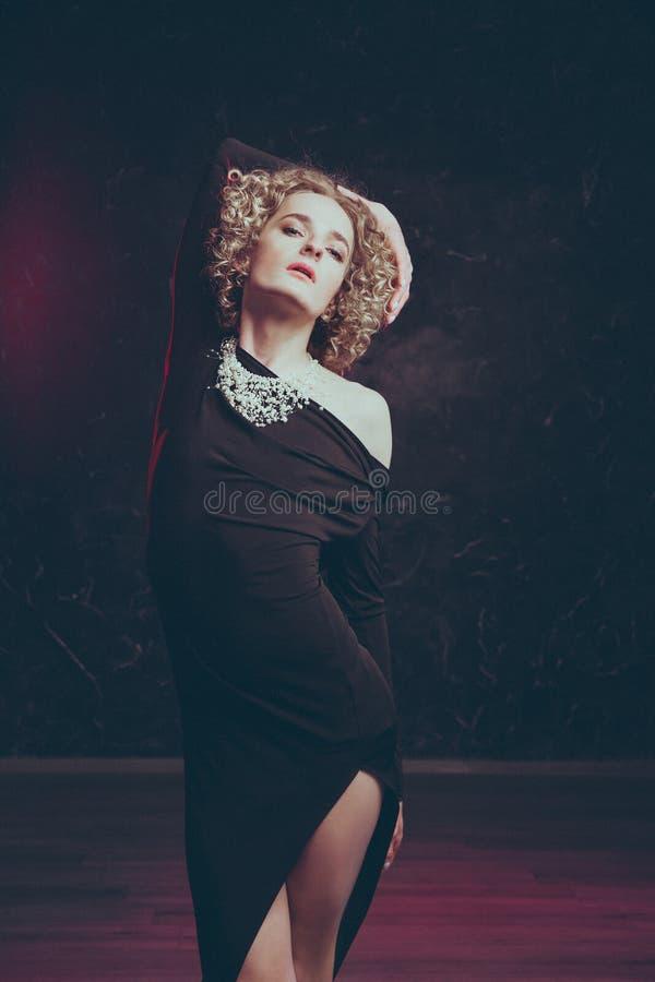 Jeune androgyn blond masculin dans l'image d'une belle femme posant sensuel dans une robe noire image stock