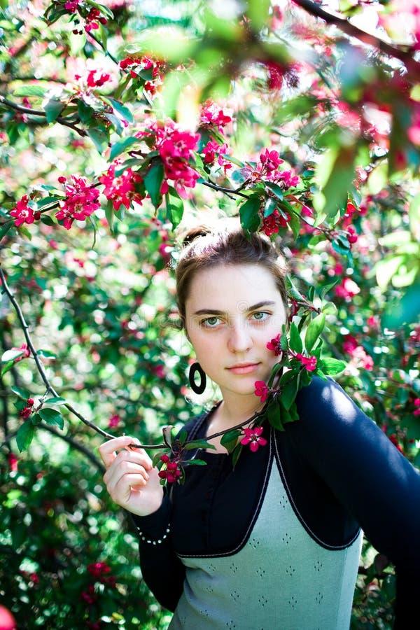 Jeune apprécier d'adolescente de l'arbre de floraison fleurit l'odeur en parc ensoleillé Beauté de printemps sans allergie photographie stock