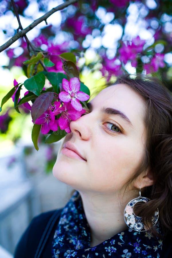 Jeune apprécier d'adolescente de l'arbre de floraison fleurit l'odeur en parc ensoleillé Beauté de printemps sans allergie photo libre de droits