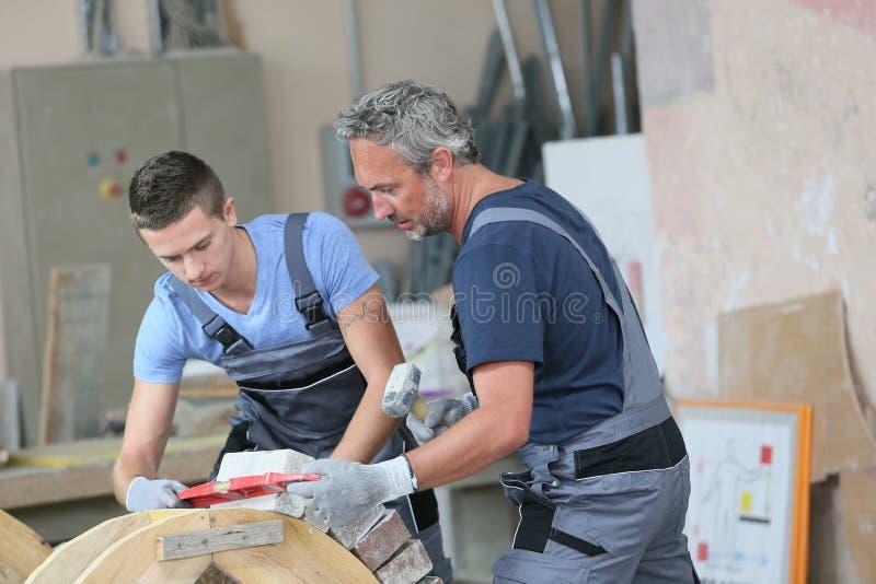 Jeune apprenti avec la couche de brique professionnelle photographie stock libre de droits