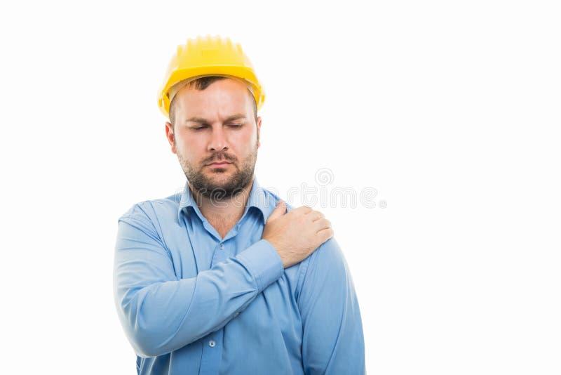 Jeune architecte avec le casque jaune montrant le geste de douleur d'épaule photographie stock libre de droits
