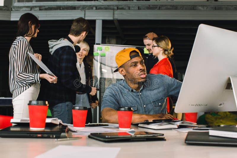 Jeune architecte masculin africain dans le fonctionnement occasionnel d'équipement au bureau sur l'ordinateur Collègues créatifs  photos stock