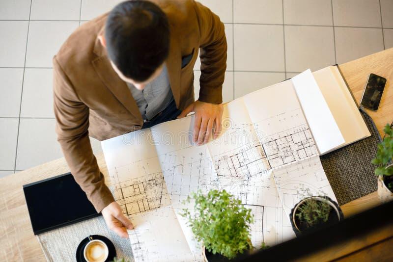 Jeune architecte regardant des plans d'étage de bâtiment Vue courbe images stock