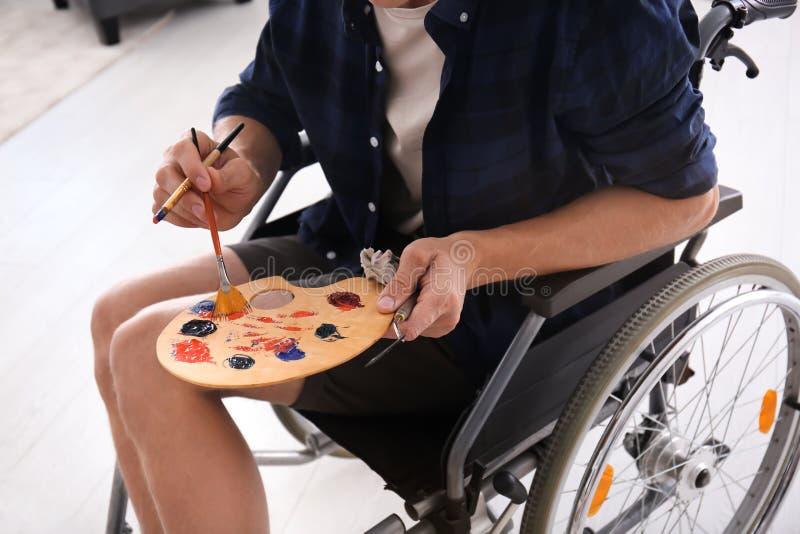 Jeune artiste dans l'image de peinture de fauteuil roulant, plan rapproché photographie stock
