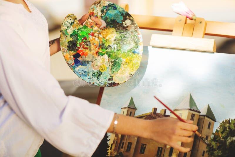 Jeune artiste de femme de brune tenant dans des mains une brosse et une palette Fin vers le haut Concept d'art image libre de droits