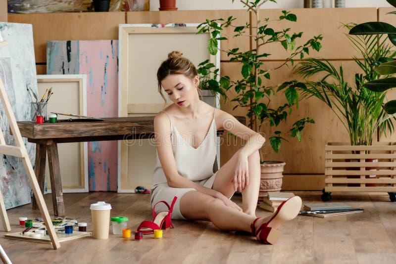 jeune artiste féminin frustrant s'asseyant sur le plancher images libres de droits