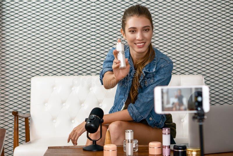 Jeune artiste maquilleuse démontrant son produit cosmétique en ligne image stock