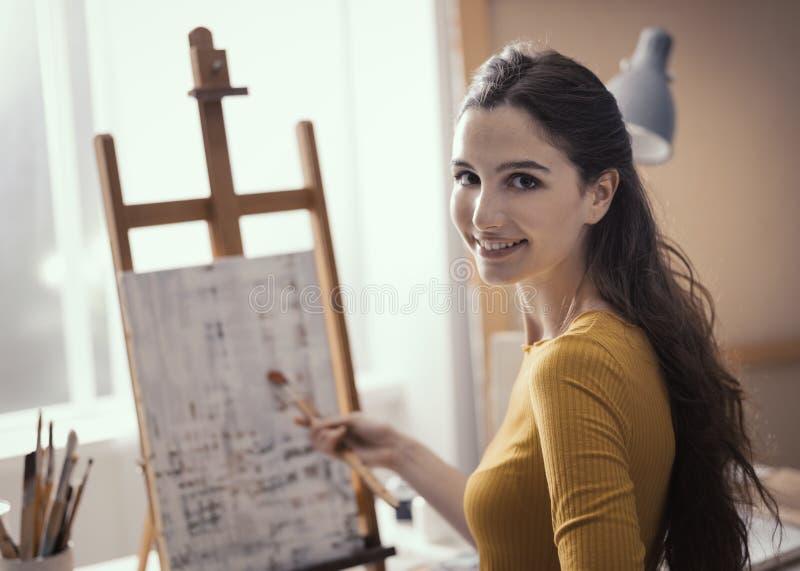 Jeune artiste travaillant à une peinture abstraite dans l'atelier image stock