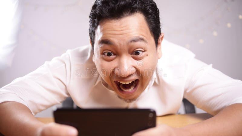 Jeune Asiatique dr?le Guy Playing Games au t?l?phone intelligent de Tablette photo stock
