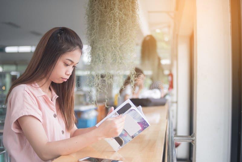 Jeune Asiatique lisant le livre se reposant à la barre de bureau photos stock
