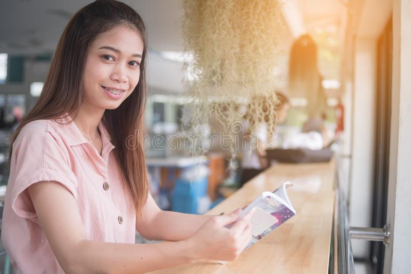 Jeune Asiatique lisant le livre se reposant ? la barre de bureau, concept d'?tude de femme photographie stock