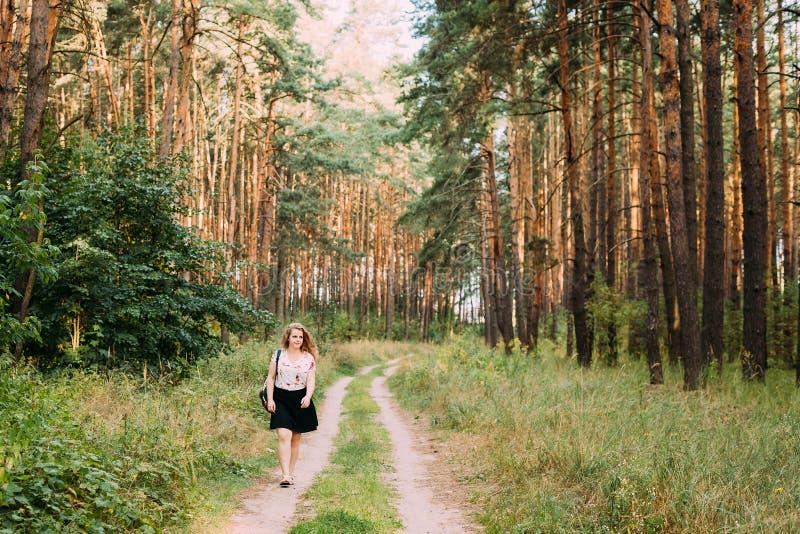 Jeune assez plus la femme de sourire heureuse caucasienne de fille de taille sur la route photos stock