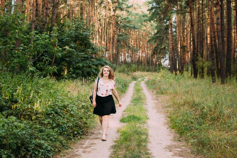 Jeune assez plus la femme de sourire heureuse caucasienne de fille de taille sur la route images libres de droits