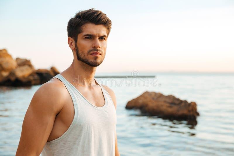 Jeune athlète bel d'homme se tenant à la plage rocheuse par photo stock