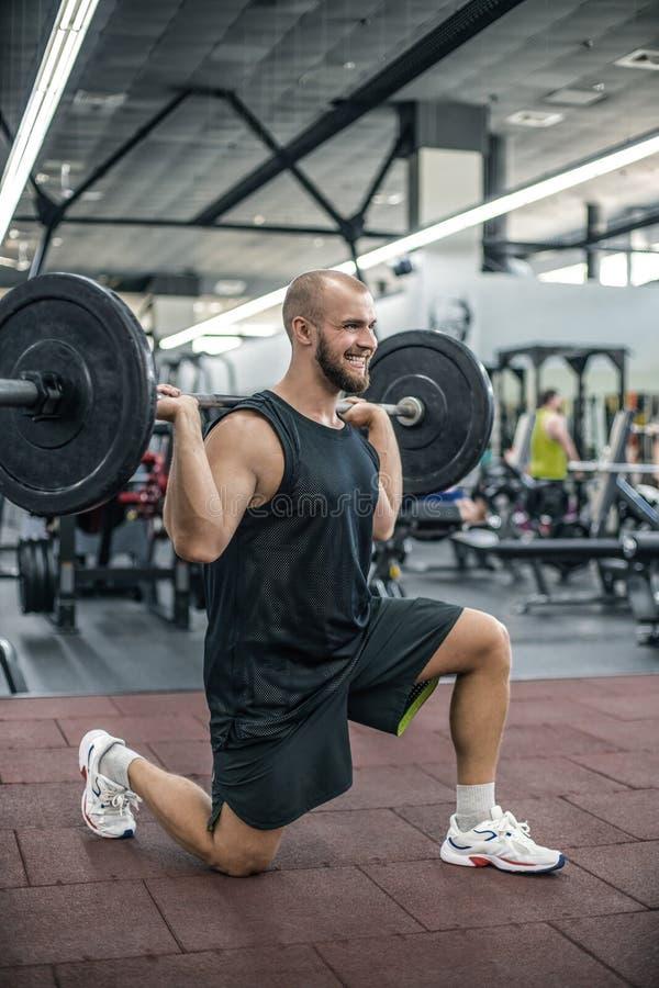 Jeune athlète convenable croisé faisant des postures accroupies avec le barbell Homme pratiquant la formation fonctionnelle Exerc photo stock