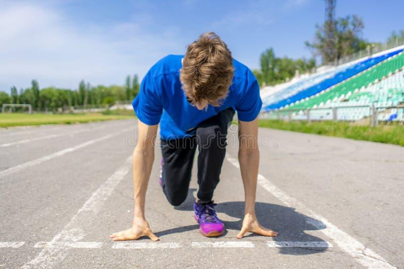Jeune athlète de coureur en basse position de début sur la voie de sports sur le stade extérieur photo stock