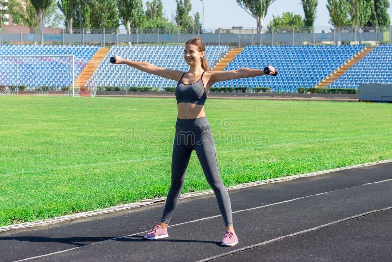 Jeune athlète féminin avec des haltères s'étendant et réchauffant sur la voie courue dans le sport de stade et le concept de form images libres de droits