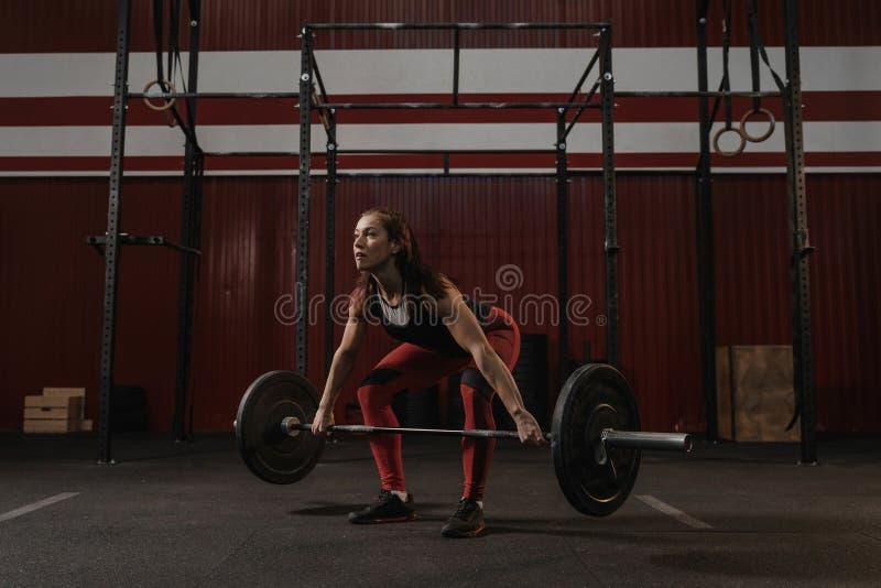Jeune athlète féminin faisant l'exercice de deadlift Femme forte soulevant le barbell lourd au gymnase de crossfit image libre de droits