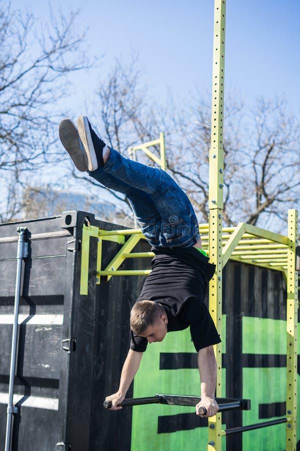 Jeune athlète faisant un support de main sur des barres parallèles dans un gymnase extérieur images libres de droits