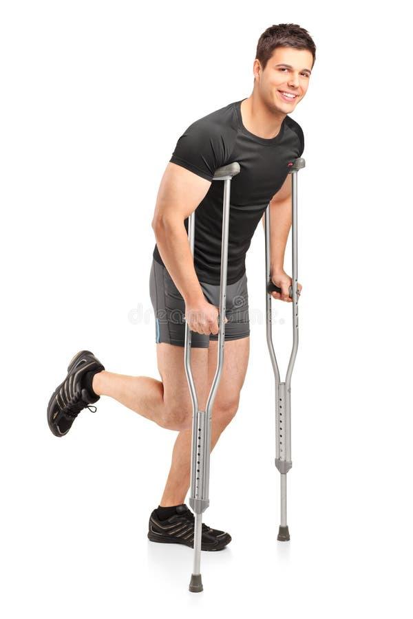 Jeune athlète masculin blessé marchant avec des béquilles image stock