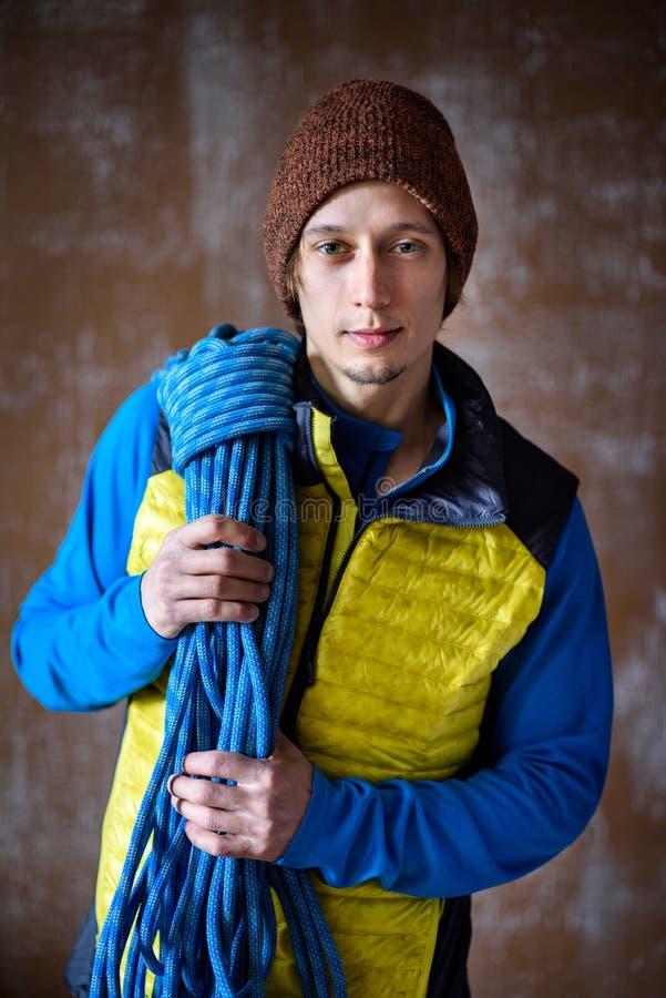 Jeune athlète masculin convenable, grimpeur de roche avec une corde, sport photographie stock libre de droits
