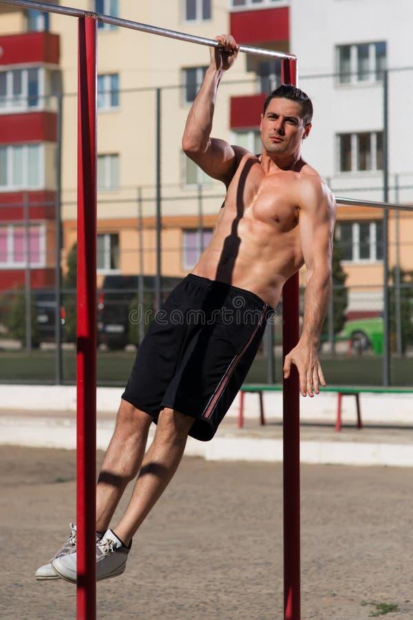 Jeune athlète musculaire faisant des exercices cabreurs accrochant avec une main droite sur une barre horizontale dans la cour image libre de droits