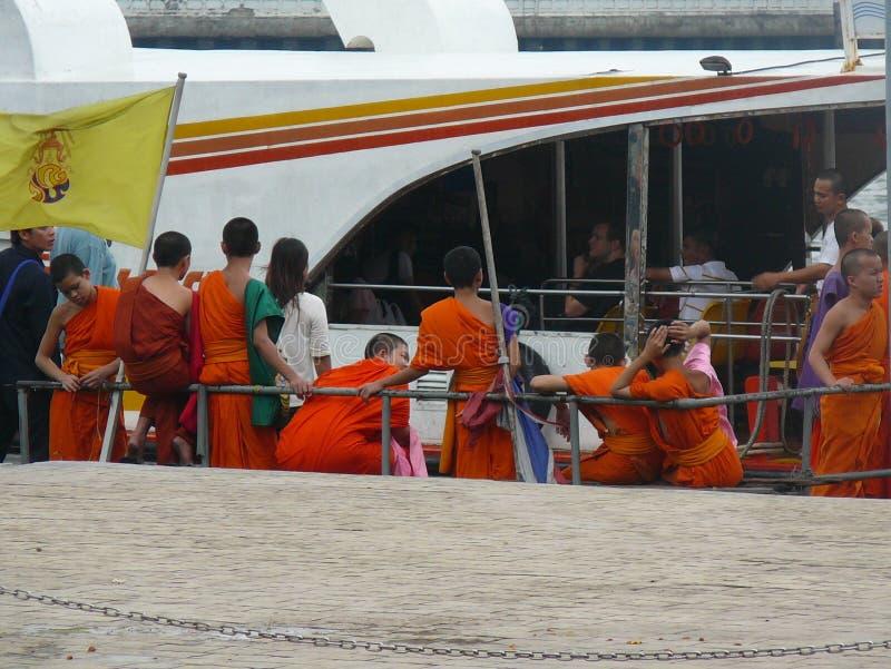 Jeune attente bouddhiste pour monter à bord du bateau photos stock