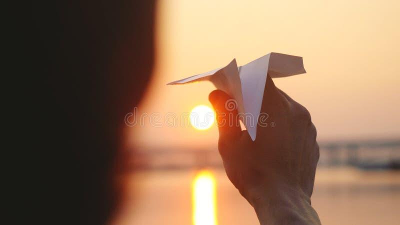 Jeune avion de papier de lancement de type contre la mer pendant le coucher du soleil avec la fusée du soleil et les réflexions d images libres de droits